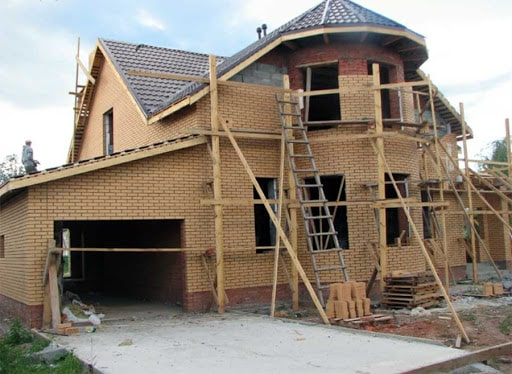 How to Budget for A New Build Home. Modern house with garage made of yellow bricks