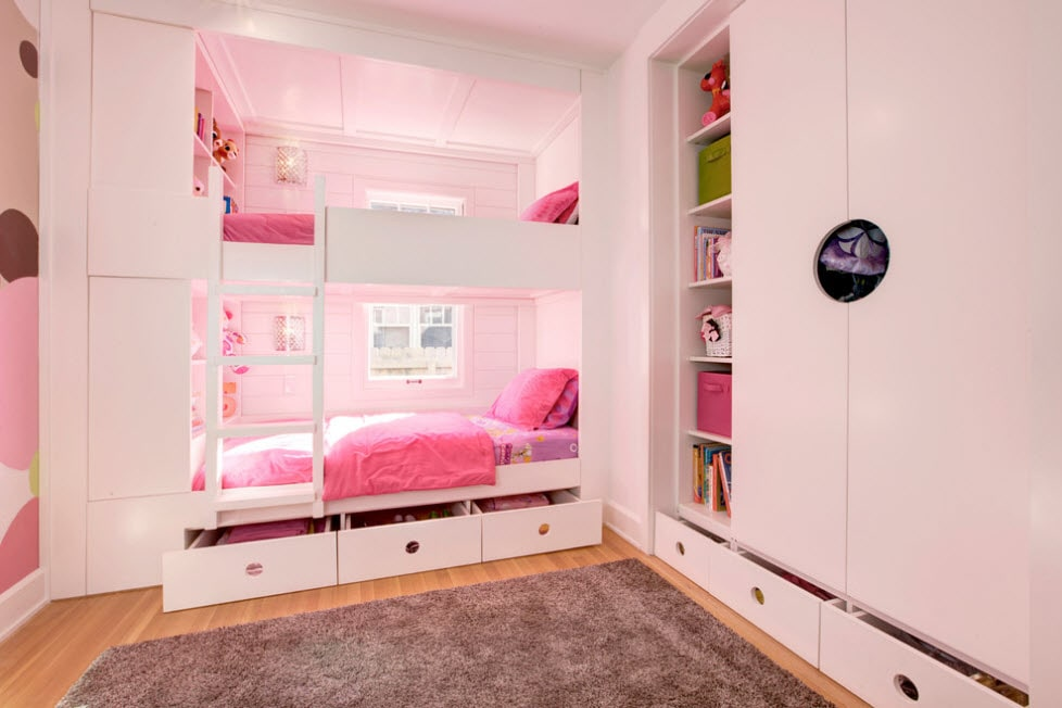 Pink colored room with white bunk bed at the window