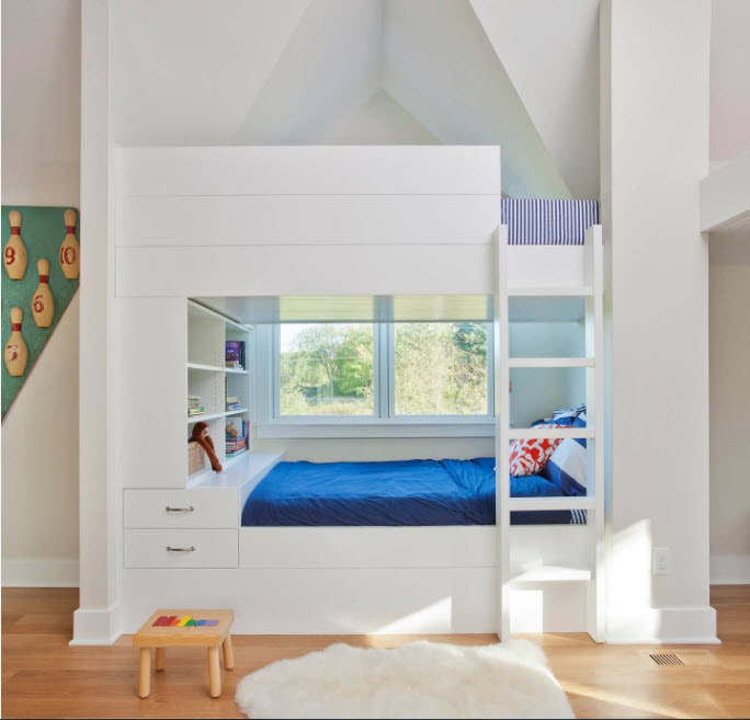 Bunk Bed as an Option to Enhance the Interior Functionality. Totally white area with blue mattress plays in contrast