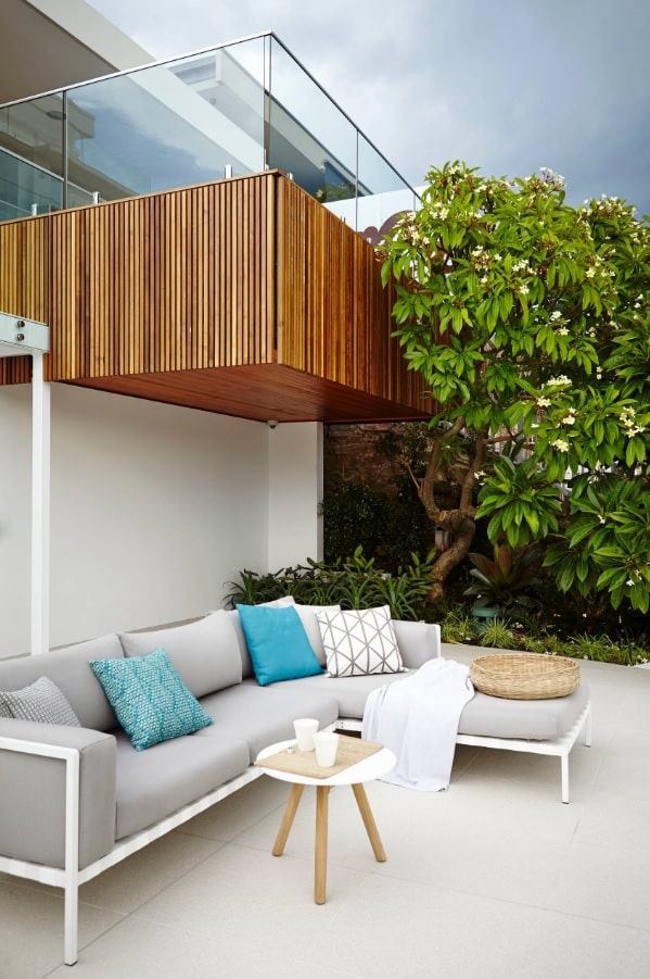 Backyard with relaxing chatting zone designed in casual style under the cantilever platform of the second level balcony
