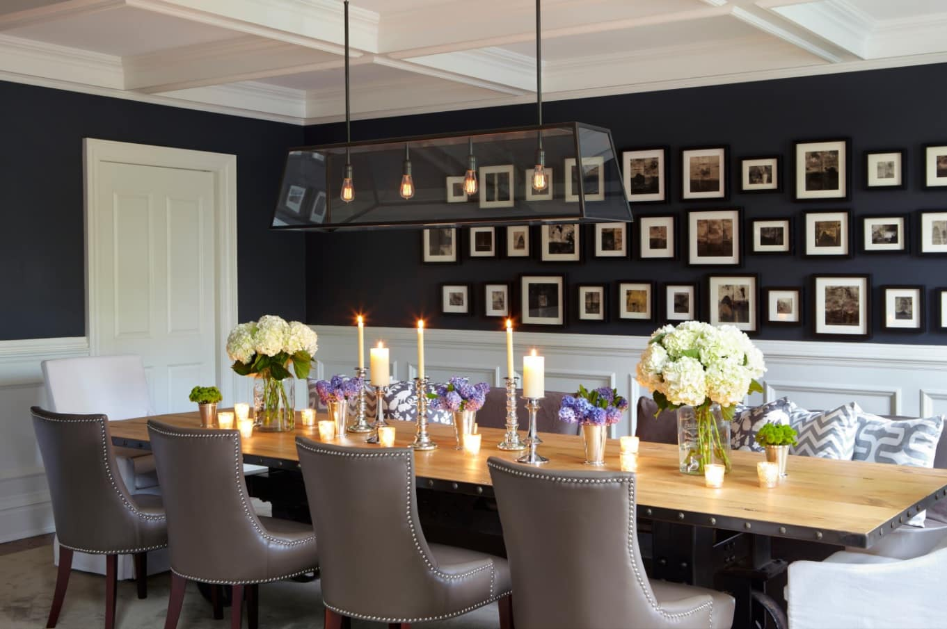 Modern Leather Dining Chairs to Complement the Interior. Grey noble riveted chairs in the space with black walls decorated with photos
