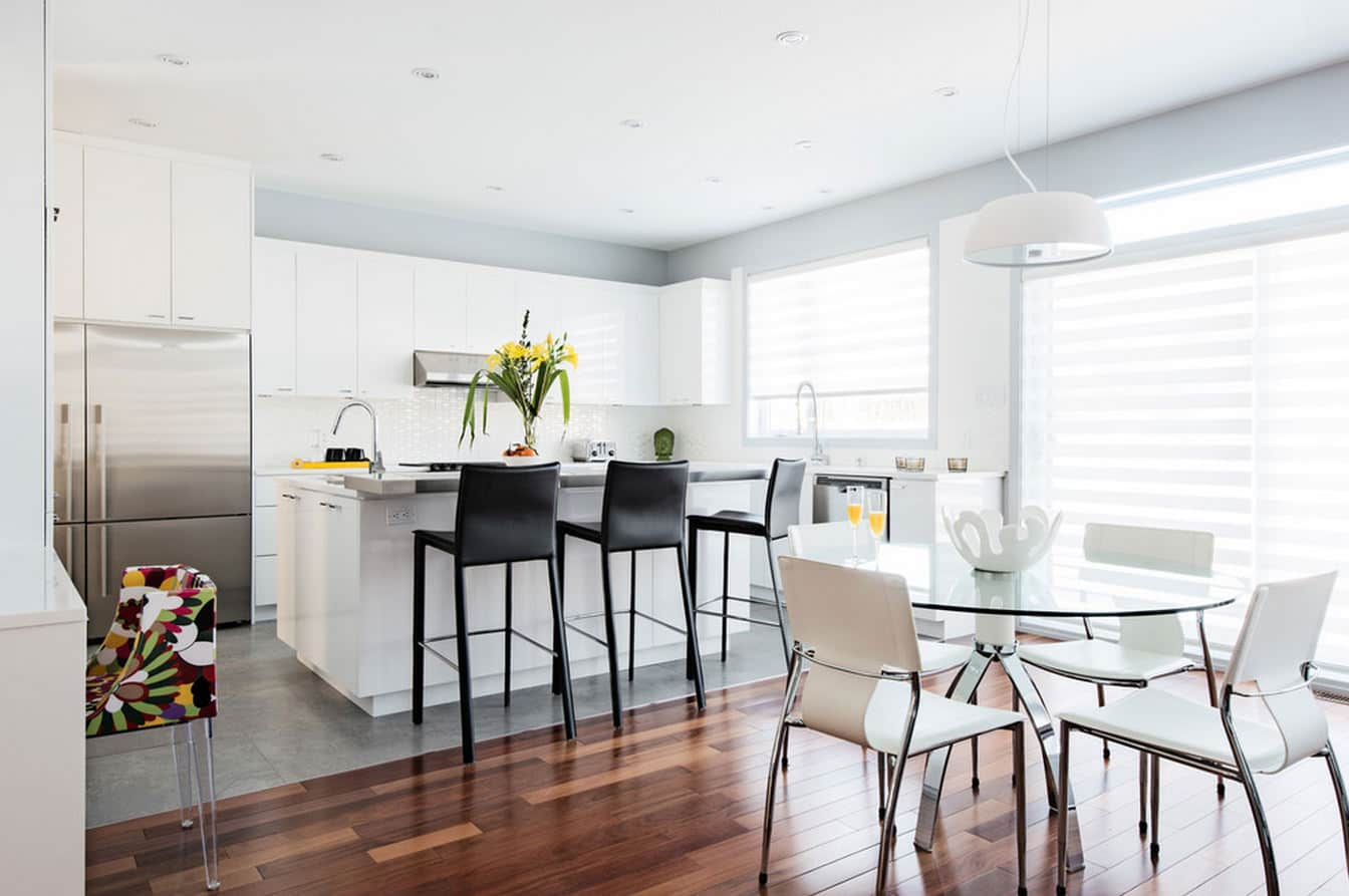 Contrasting floor and chairs in the totally white and steel modern interior of the open layout cottage