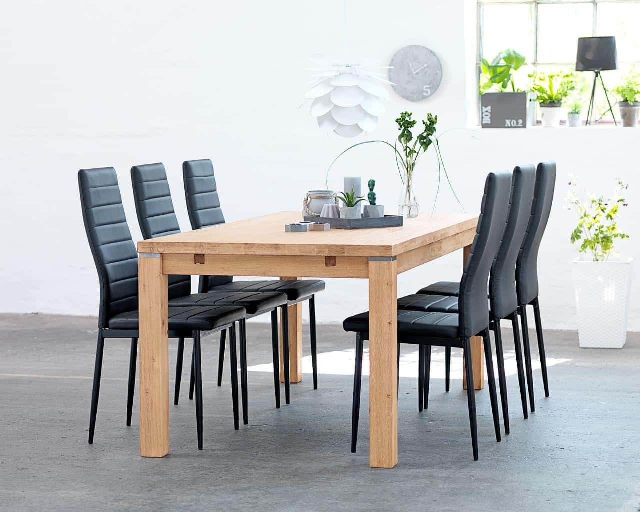 Modern faux leather black chair set at the simple light wooden table in the totally white room