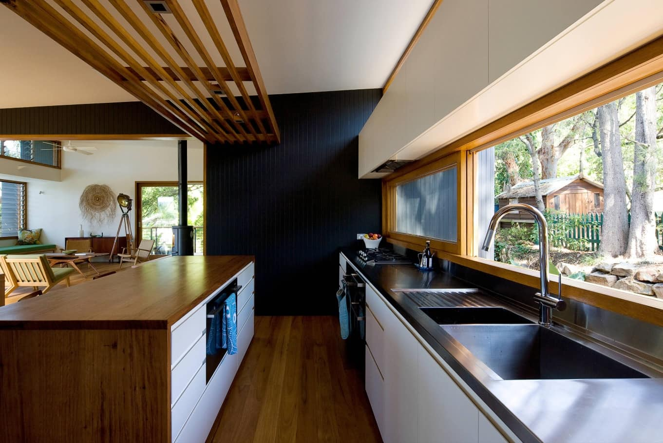 Wooden slatted panel above the kitchen island and the wooden window frame and floor
