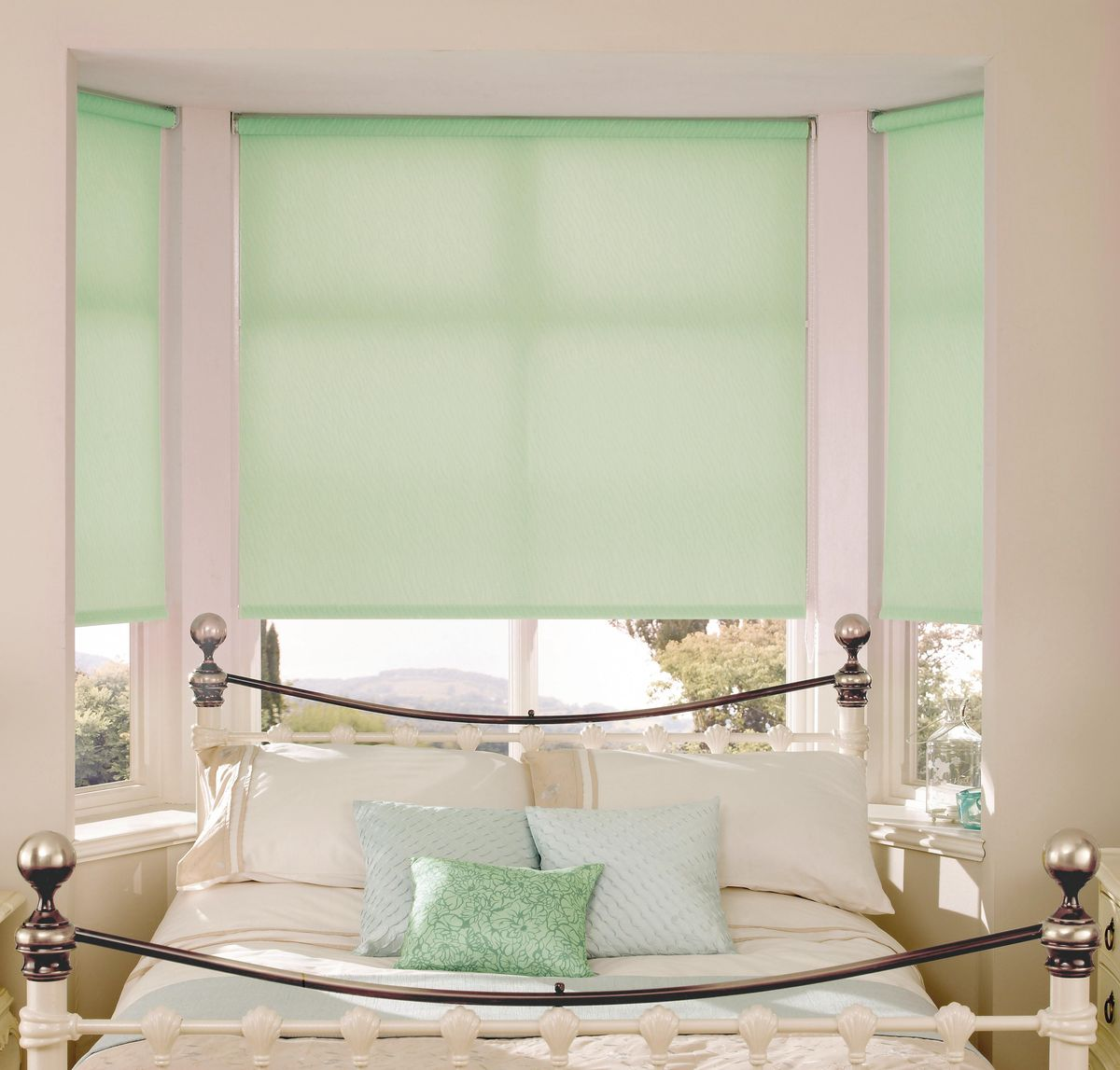 Roller Blinds: Practical and Good Looking Window Treatment. Bay window with the light emerald translucent blinds