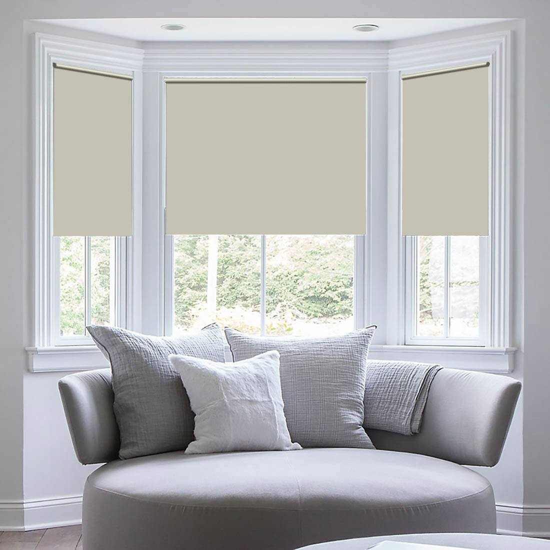 Gray sunny lit bay window with mild colored roller blinds