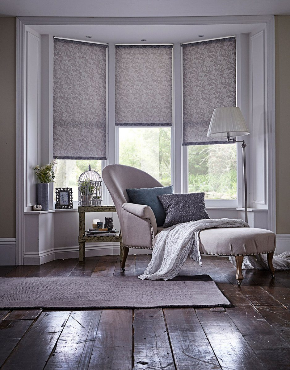 Gray colored roller blinds with darker texture and rough treated floor for unique designed living room with leisure chair