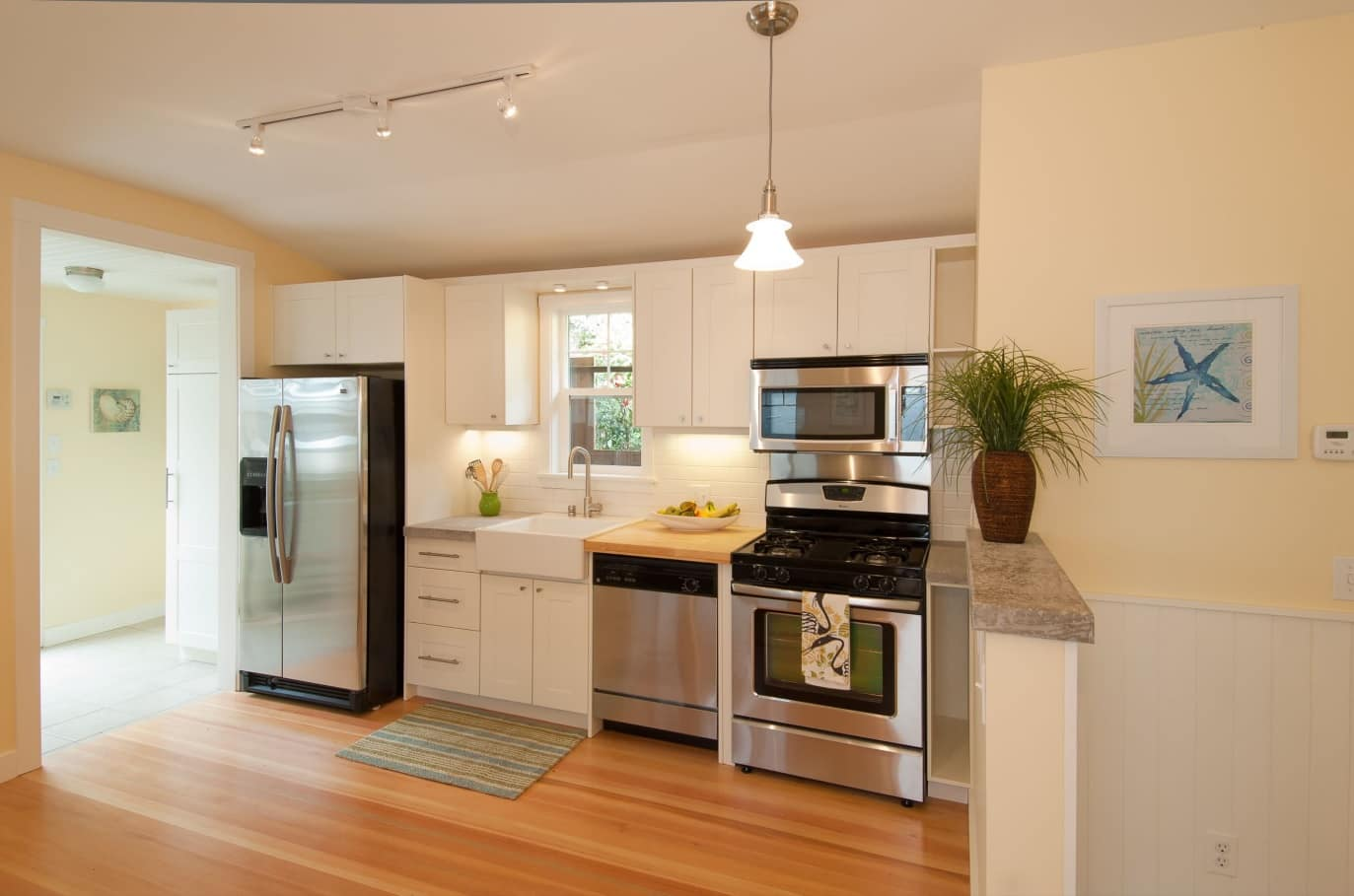 Seasonal Cleaning Tips. Great neat kitchen design with hardwood floor and steel surfaces of appliances
