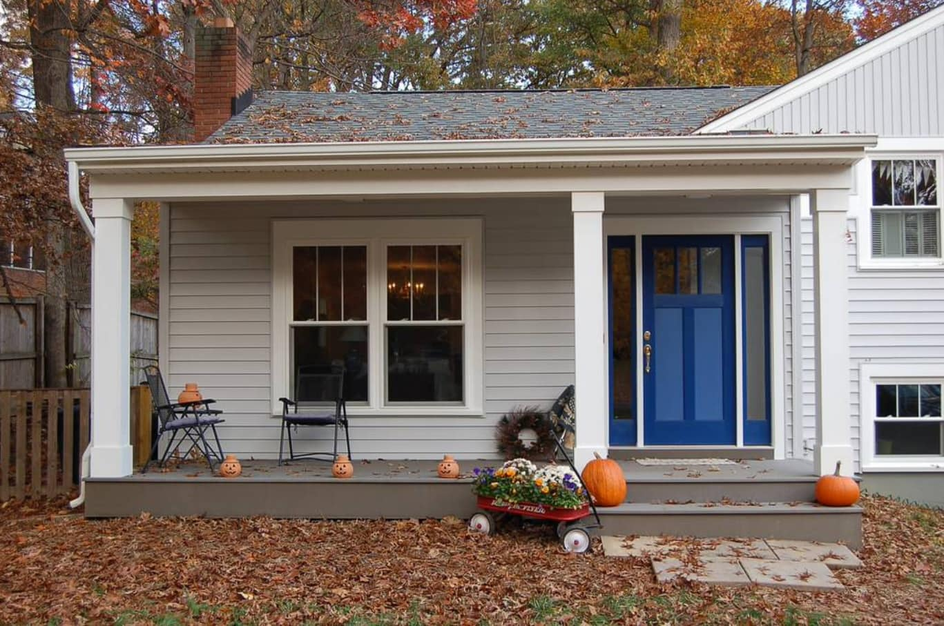 Seasonal Cleaning Tips. Pumpkins at the porch of the regular designed cottage with gray sheathing