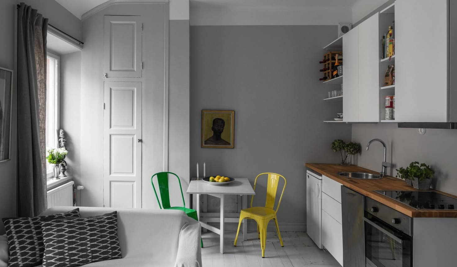 10 Tips on Remodeling Kitchens for New Homeowners. Gray wall and colorful chairs for small dining area