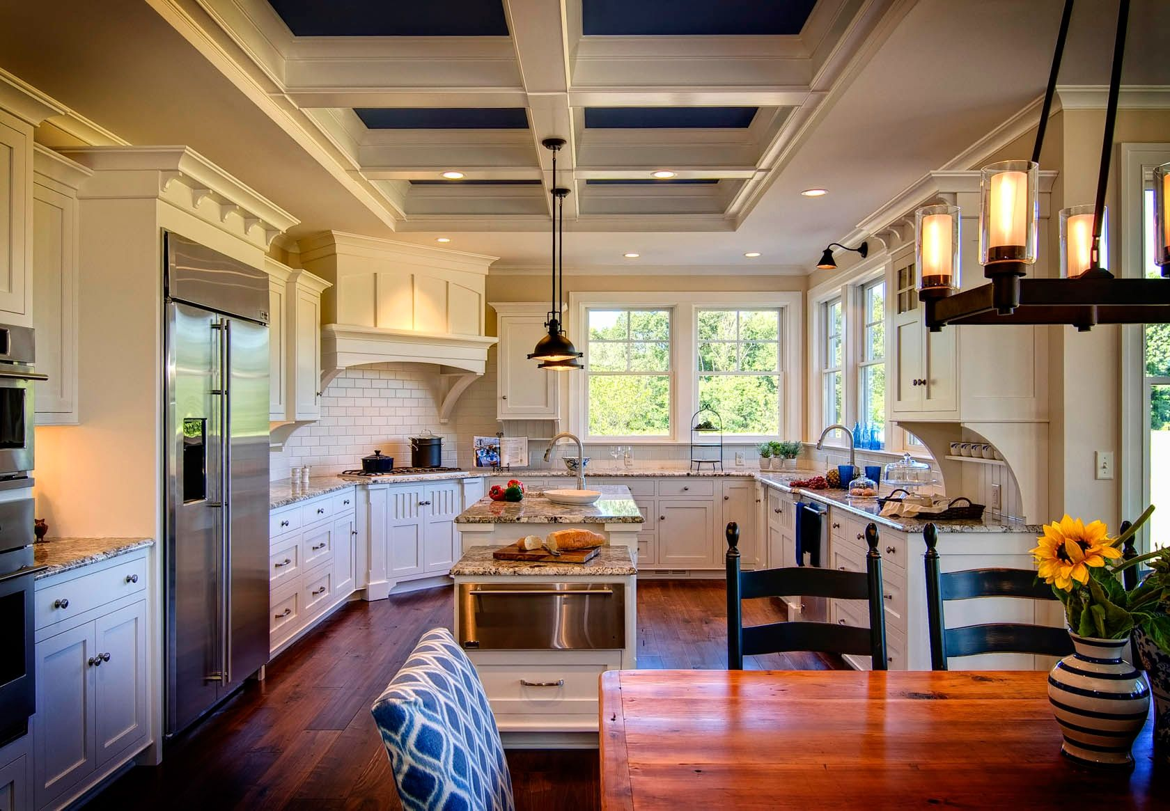 Coffered ceiling with accentual black for large colonial styled kitchen with black chairs too