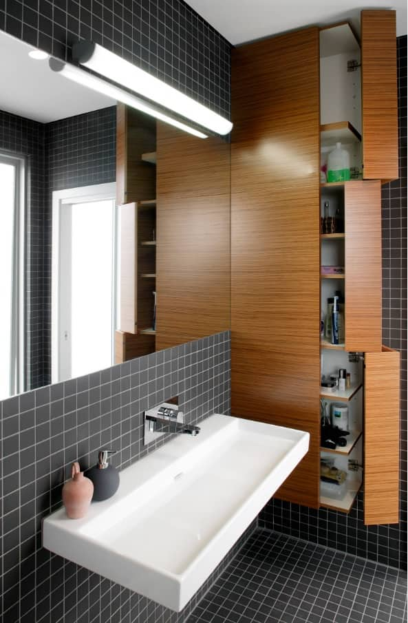Great combination of shallow black tile with wooden furniture facades in the urban styled bathroom