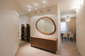 Marvelous interior design of the hallway with large oval mirror with wooden frame
