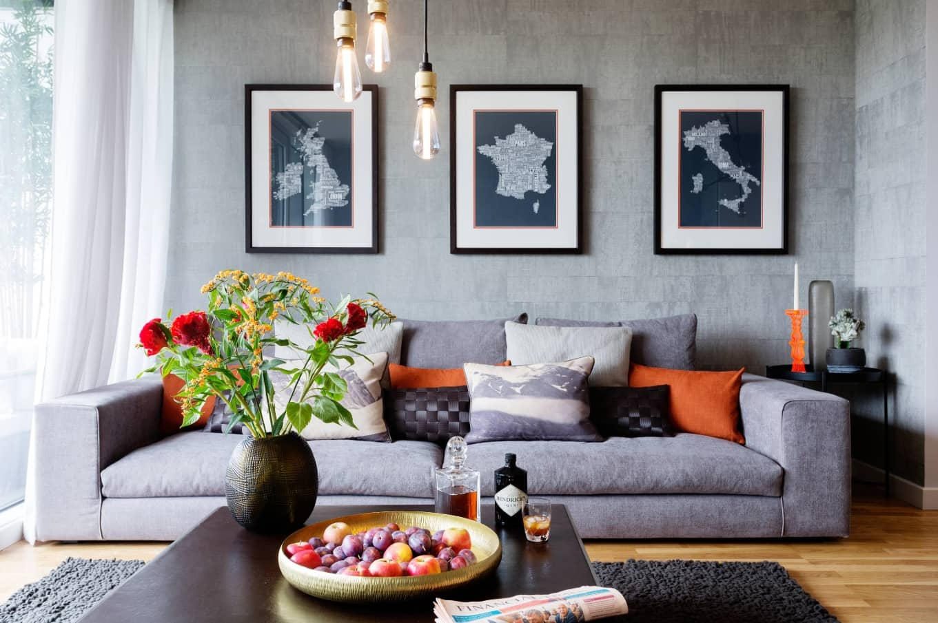 Great decorated modern living room with pendant lights, faux concrete painted walls and pictures with European countries