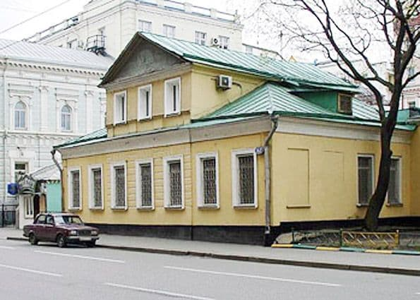 Russian old house painted yellow with mezzanine and green roof