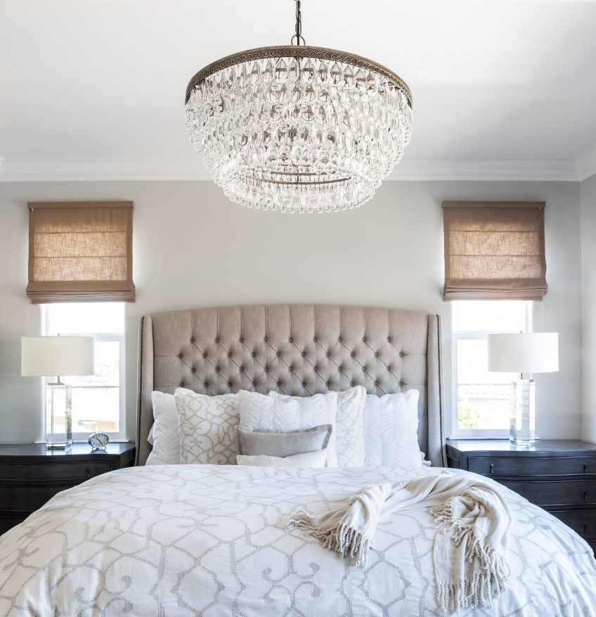 Round crystal chandelier over the king size bed