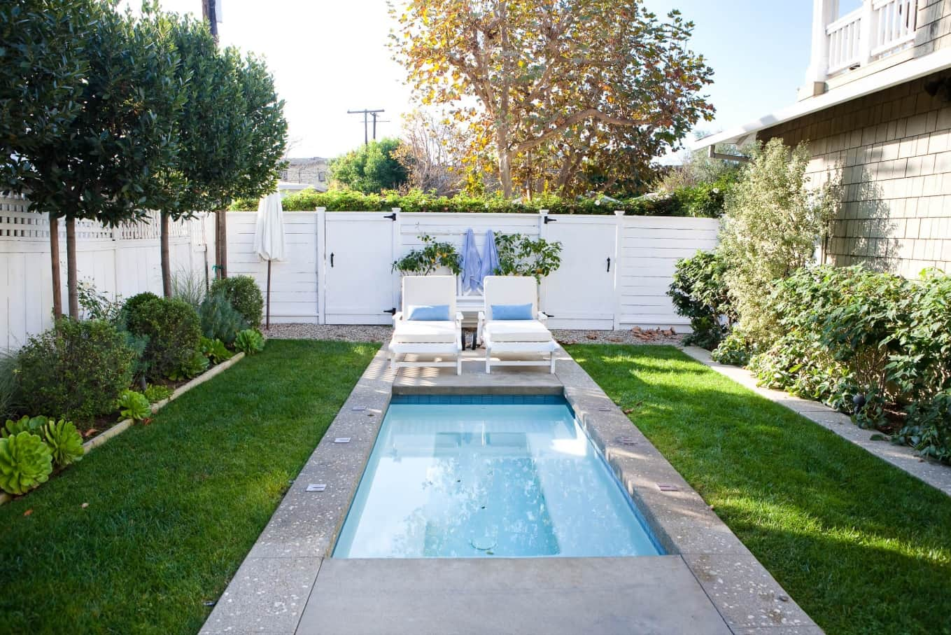8 Steps to Take to Prepare Your Pool for the Summer. Concrete brimmed pool with white sunbeds near