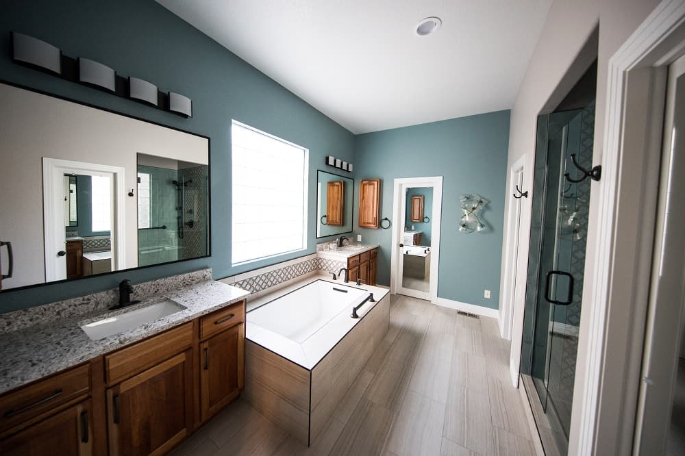 5 Reasons Why Timber Vanities are Best for Your Bathroom. Blue walls and separately standing wood trimmed bathtub