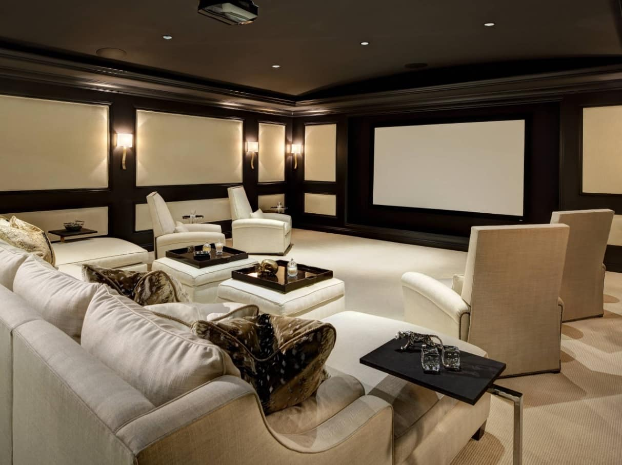 Dark colored home cinema with white leather sofas and armchairs
