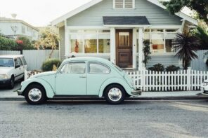 How To Make a New House Look Old. Classic American suburban house with VW Beetle at the fence
