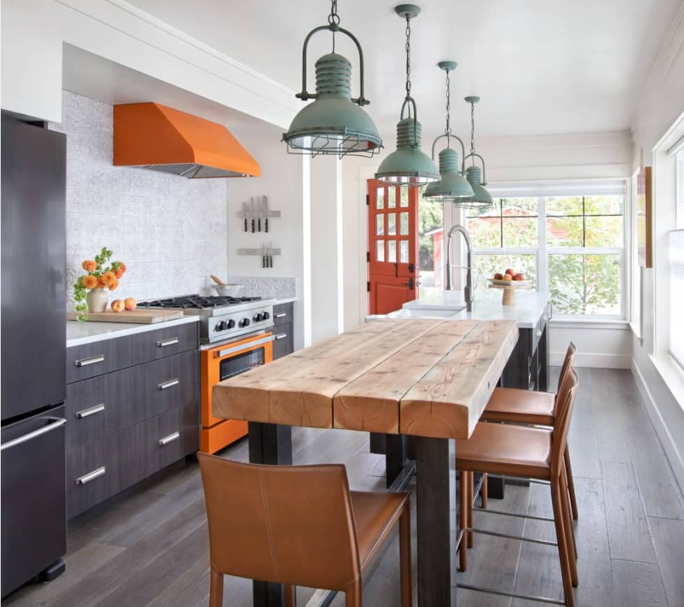 Achieving a Rustic Look in Your Urban Lifestyle. Great barn style for colorfully decorated largekitchen with orange touch