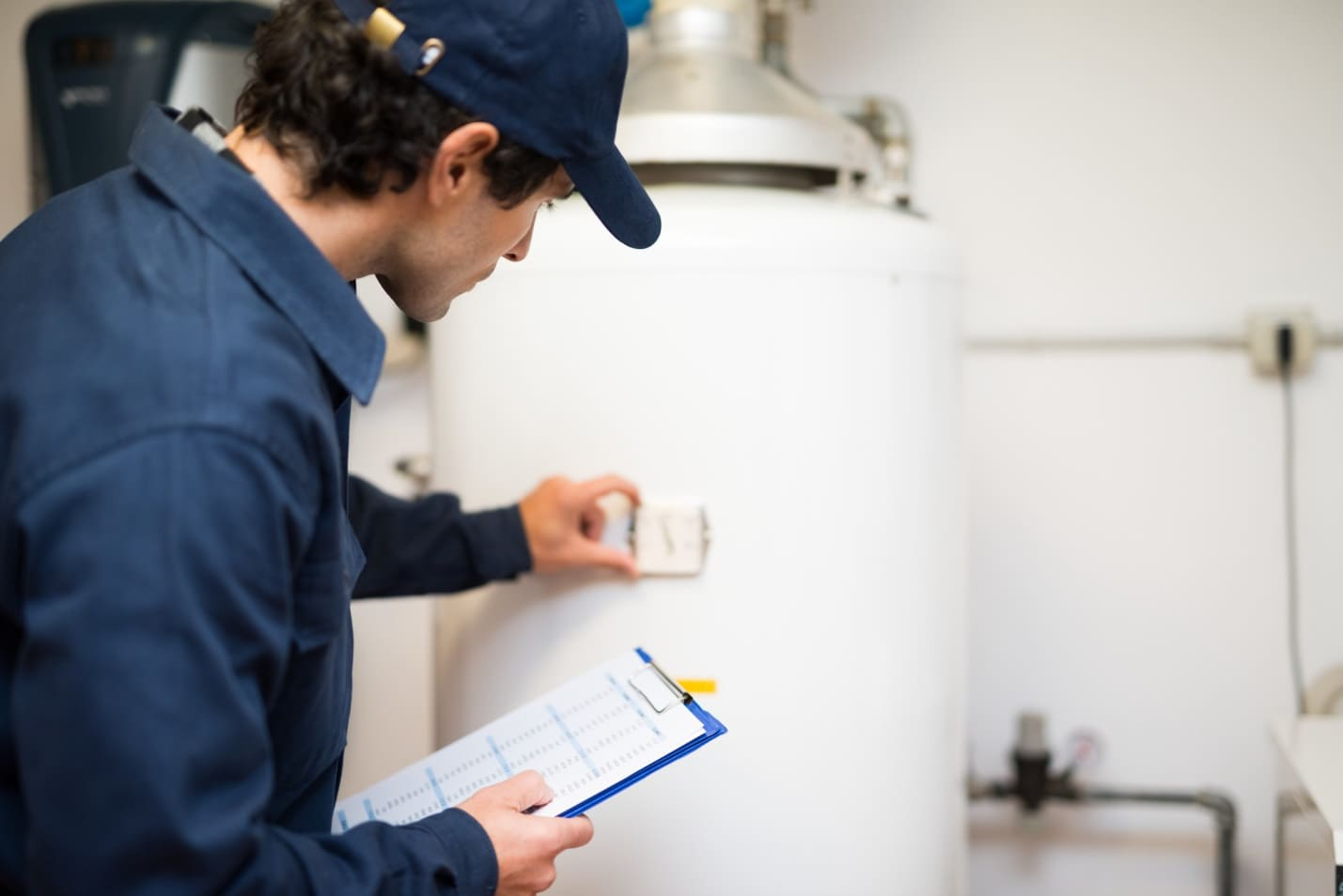 What's the Average Life Expectancy of a Water Heater? The worker estimates tank condition