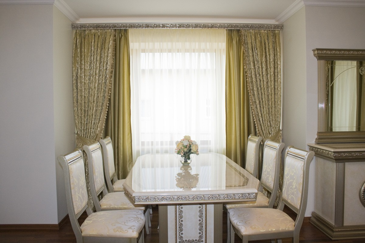 Dining room with greenish curtains and chic leather upholstered chair group