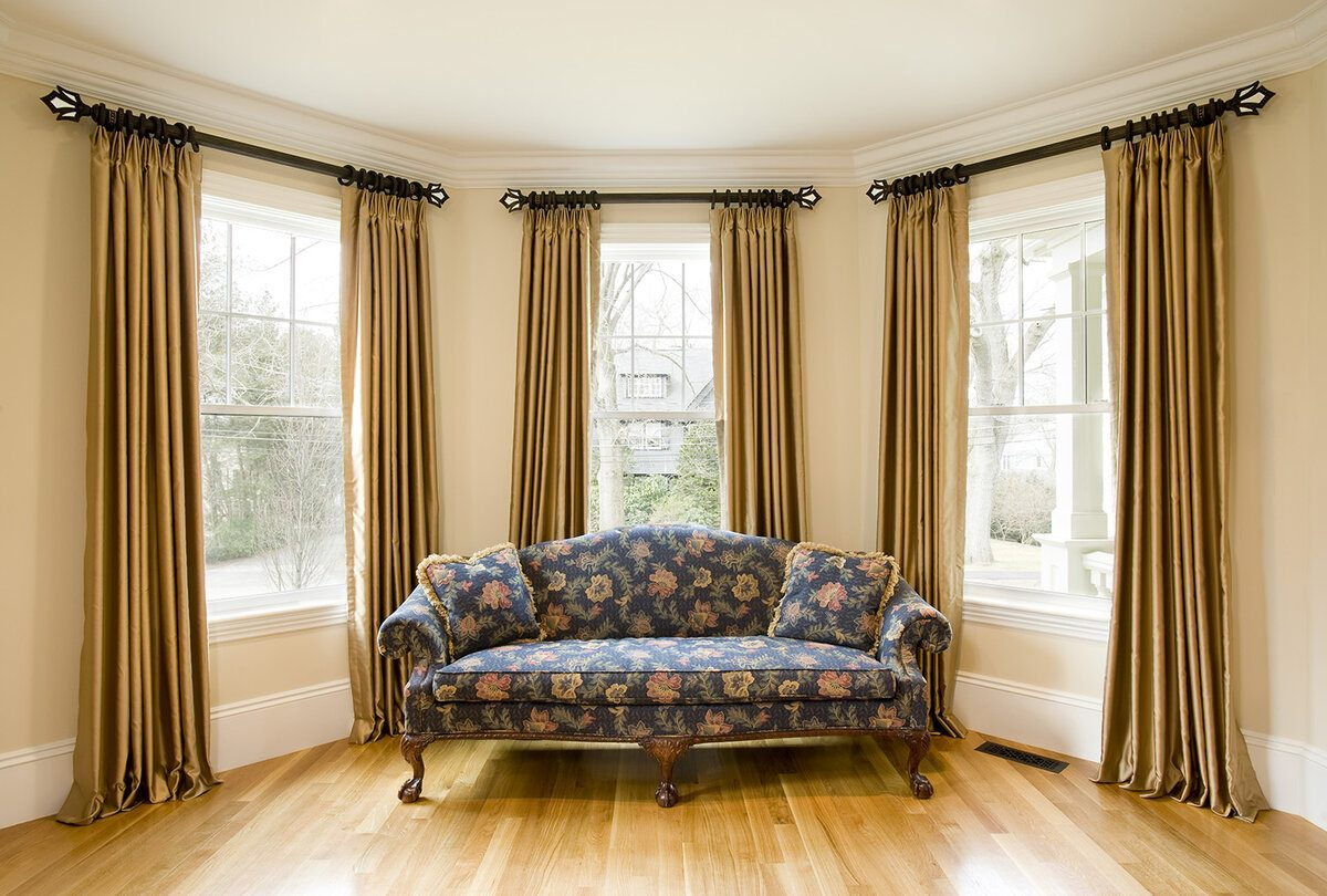 Curtains Rods: Types, Production Materials, Fastening Overview. Bay window and light hardwood floor and the sofa