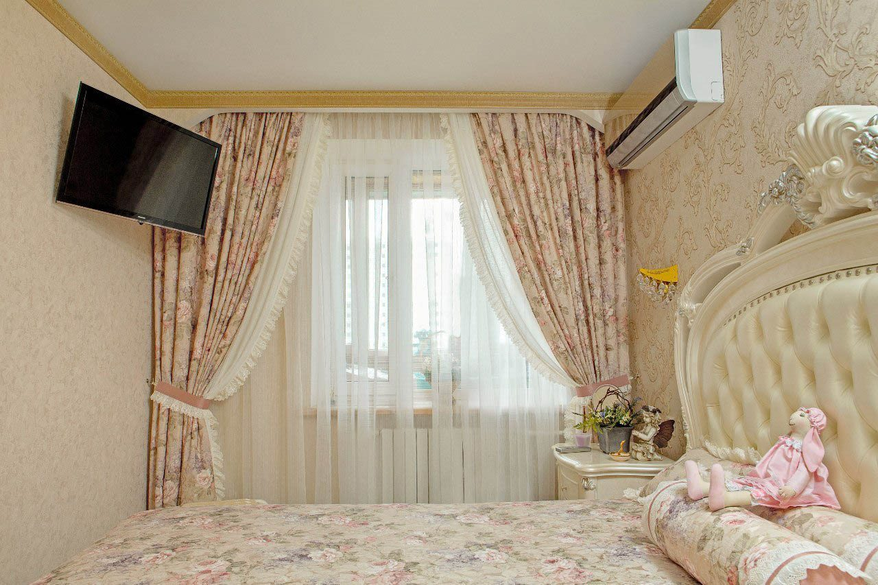 Woman's boudoir with heavy curtains on the window and suspended LED TV