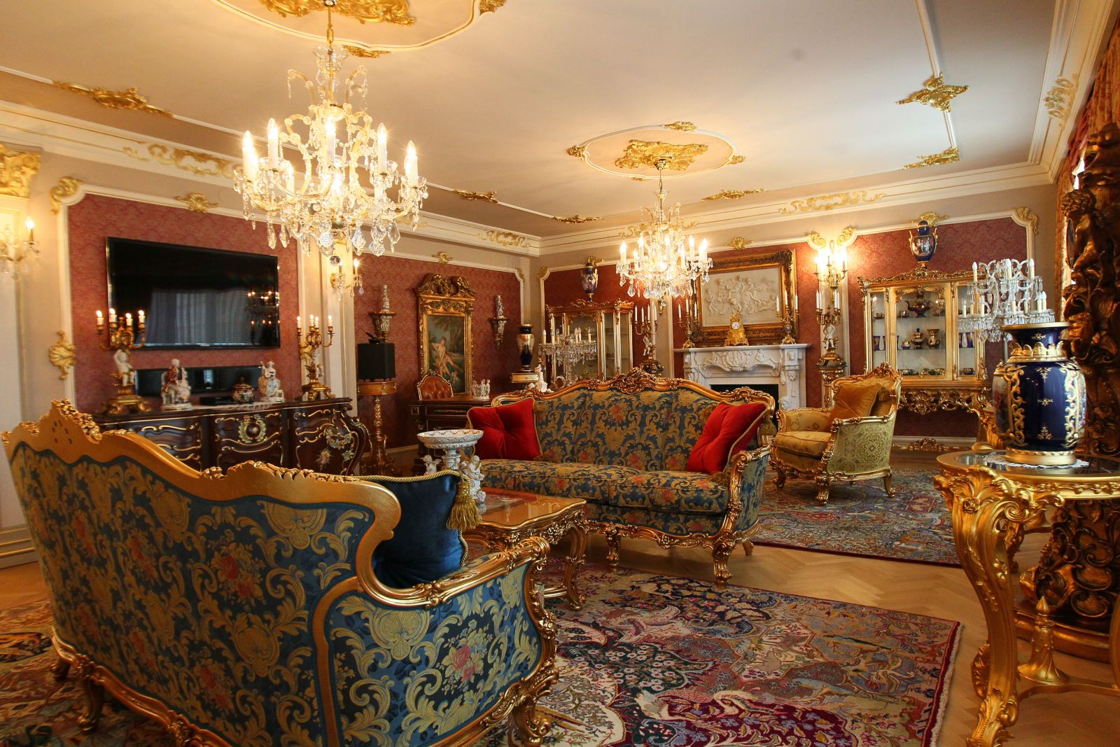 Grandeur atmosphere of the living room with richly recorated carpet, crystal chandelier and carved upholstered furniture