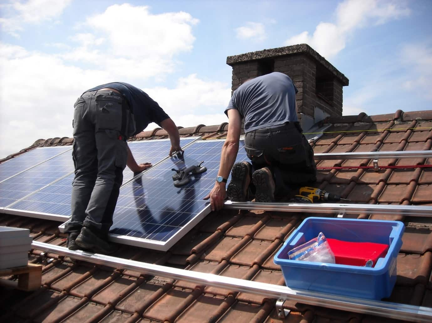 Breaking Boundaries: Future-Proof Your House with Solar Panels. Workers installing solar panels at the roof on special guides
