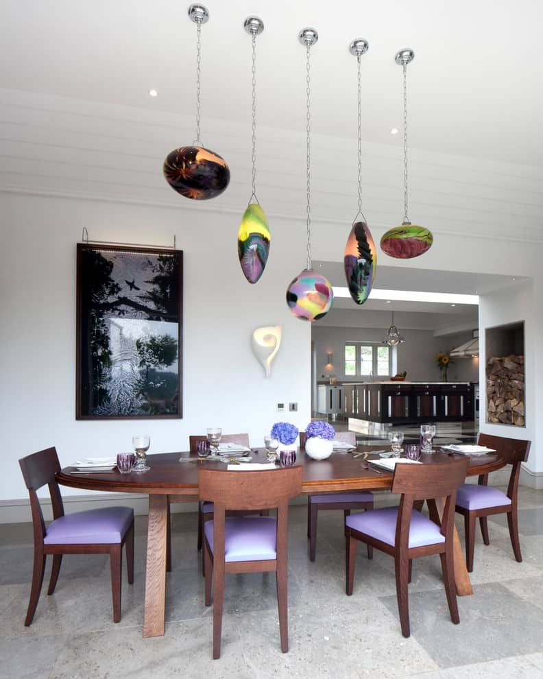 Multi-Level Lighting as Effective Way to Set Accents and Emphasize Interior. Great kitchen design with colorful chair seats and pendant lamps over the table