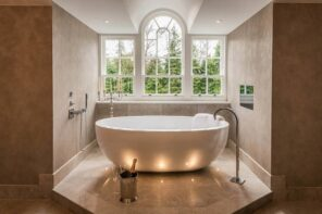 Multi-Level Lighting as Effective Way to Set Accents and Emphasize Interior. Arched window and the eggshell bathtub in the limelight of the spacious bathroom
