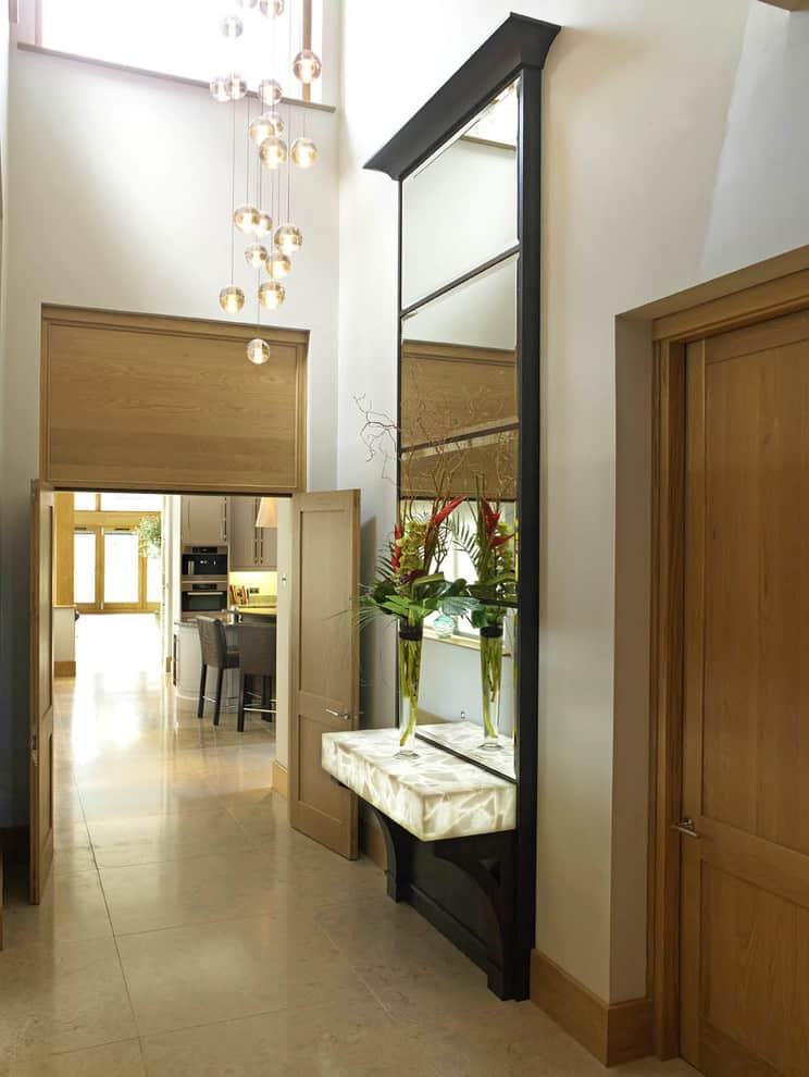 Large mirror and suspended lighting balls chendelier in the corridor