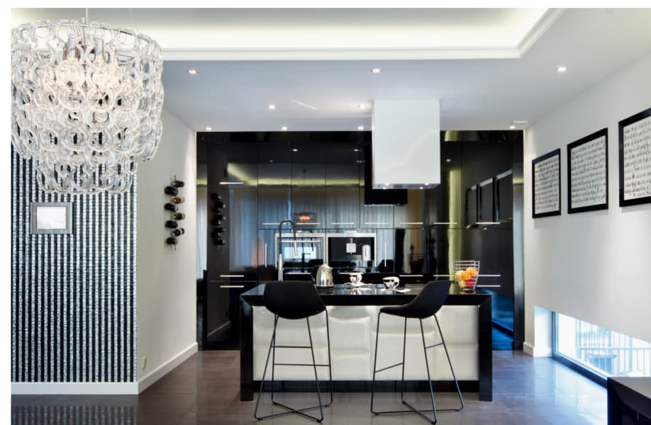 Modern white and black kitchen design with dark countertops and chairs at the backdrop of white walls