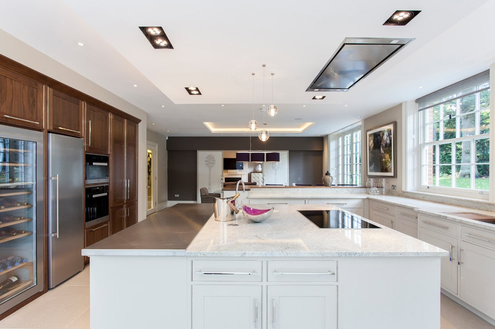 Ideally white kitchen emphasized by huge central island and complex lighting