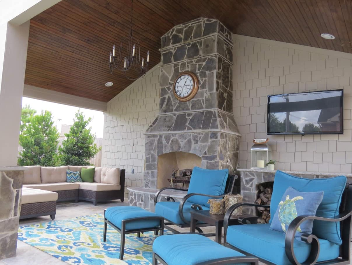 How To Create A Functional Patio Space. Stone cladded fireplace and blue upholstered furniture