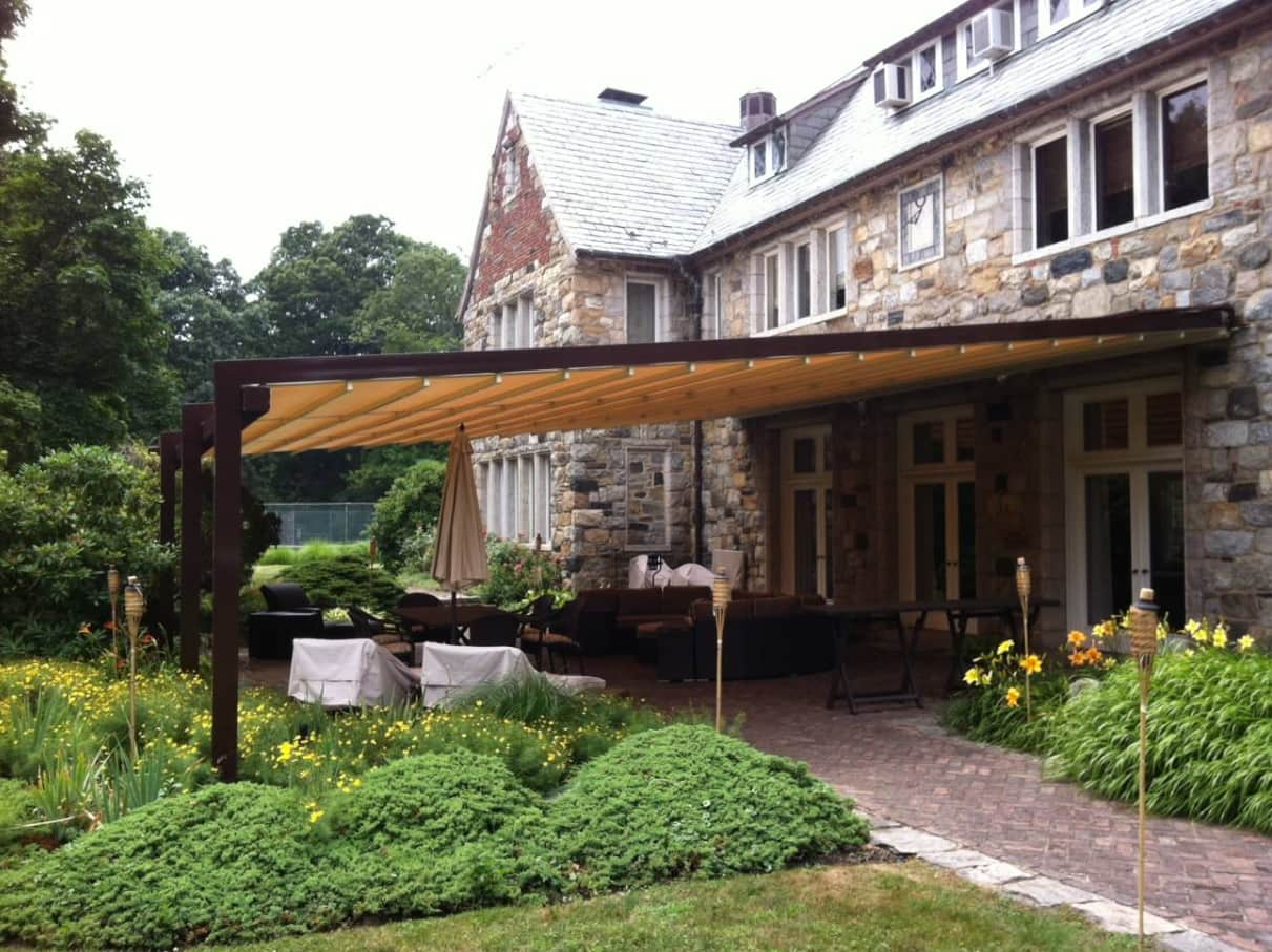How to Choose Awnings for Your Garden. Tudor styled house with large patio at the backyard