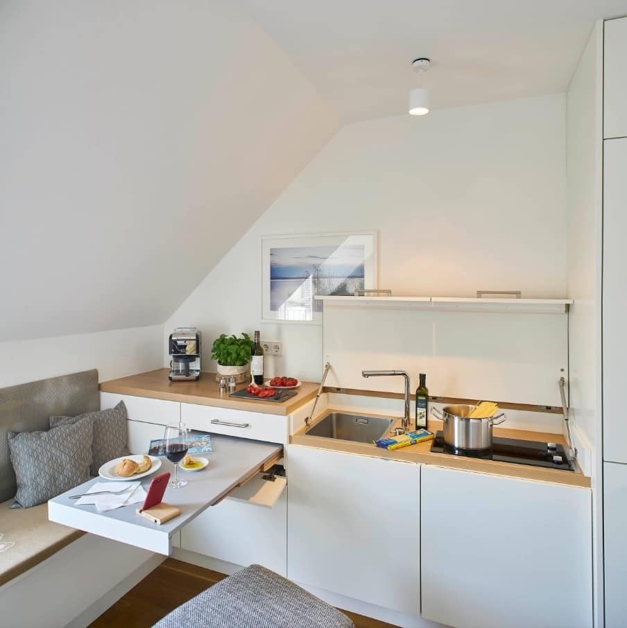 Why an Apartment is the Best Way to Live in Downtown. Universal design for the small modular kitchen at the small white painted space