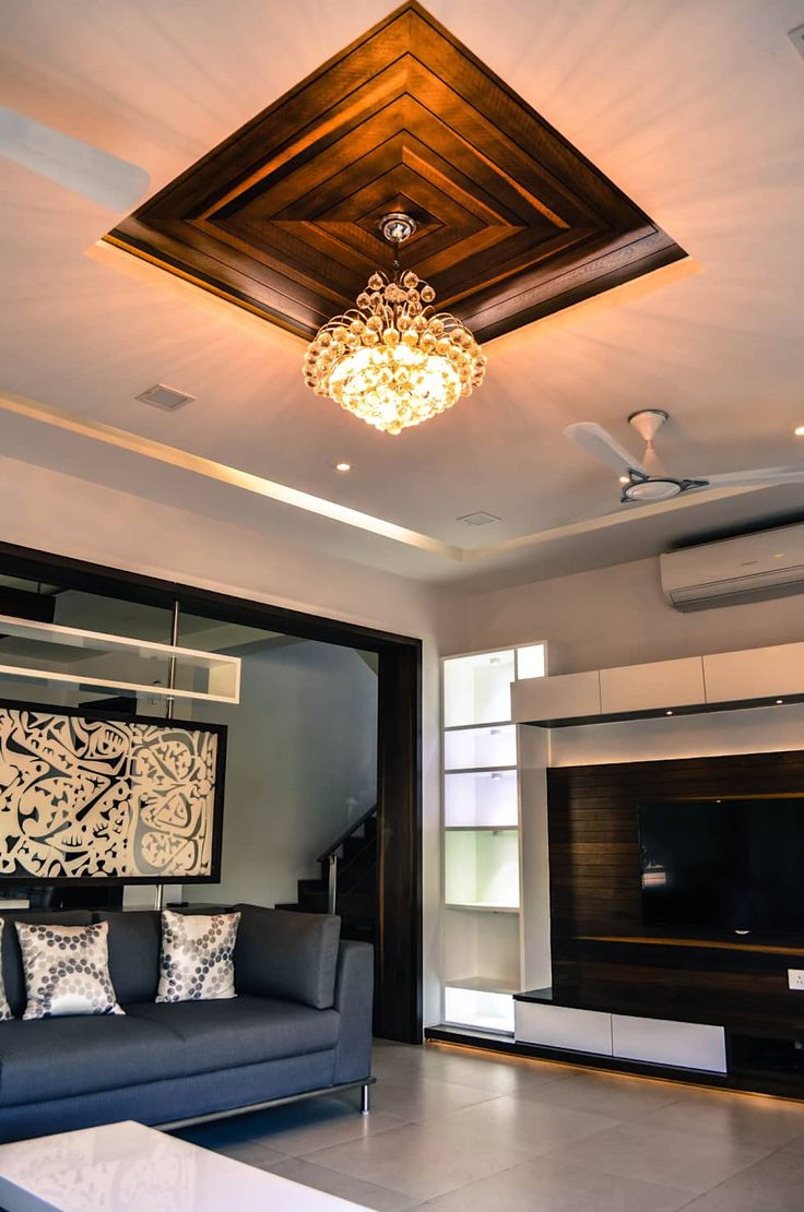 Skillful ceiling design with multilevel inlays in black to contrast with austere living room walls