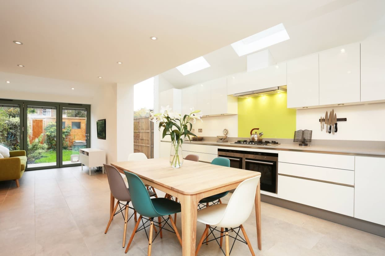 Skylights and pastel color paletet for spacious contempoarry kitchen with dining zone