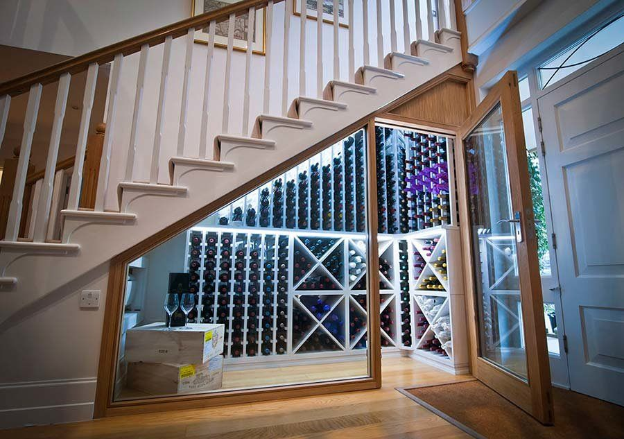 Lighted wine cellar under the stairs with glass case