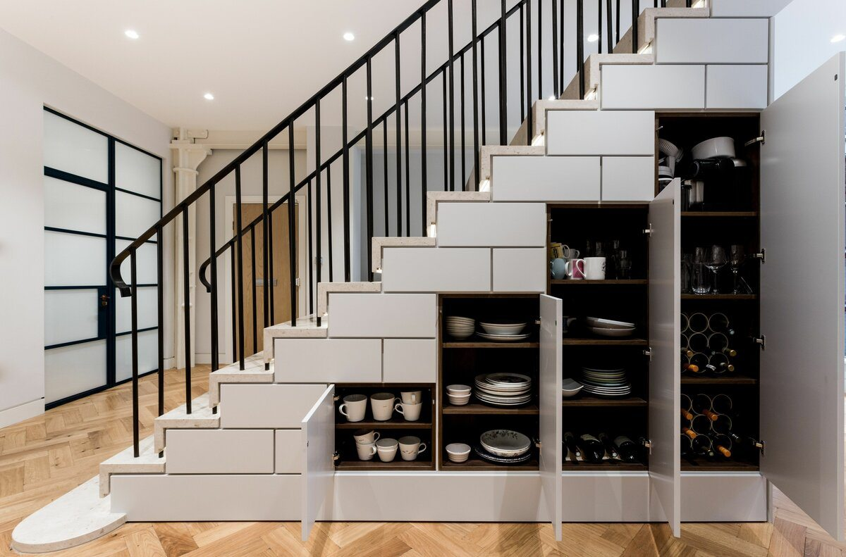 Masterful designed cabinets for cutlery and dishes under the stairs