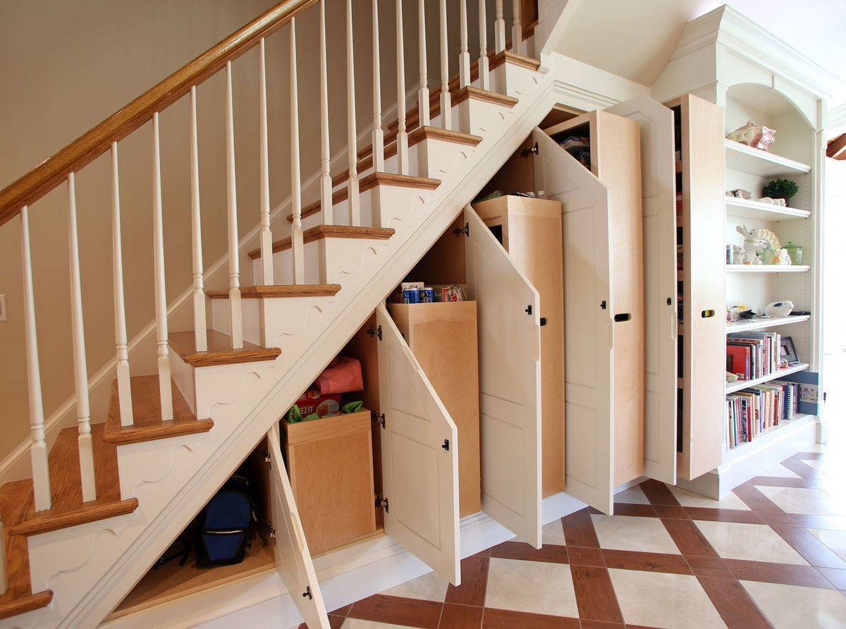 Many cabinets with regular doors for storage under the staircase