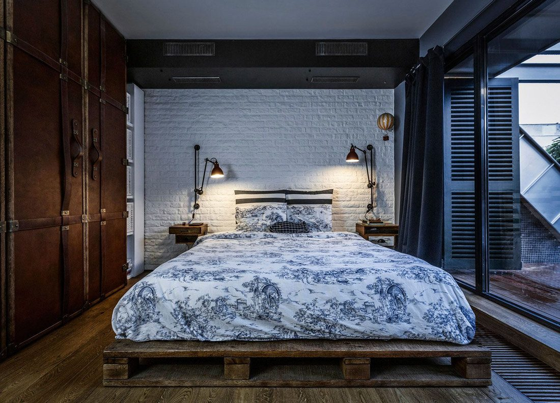 Reusable pallet bed platform and white painted headboard wall