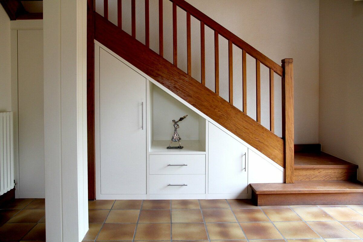 Storage under the Staircase: Different Ideas and Functional Spaces. Simple idea of the cabinet with white facades