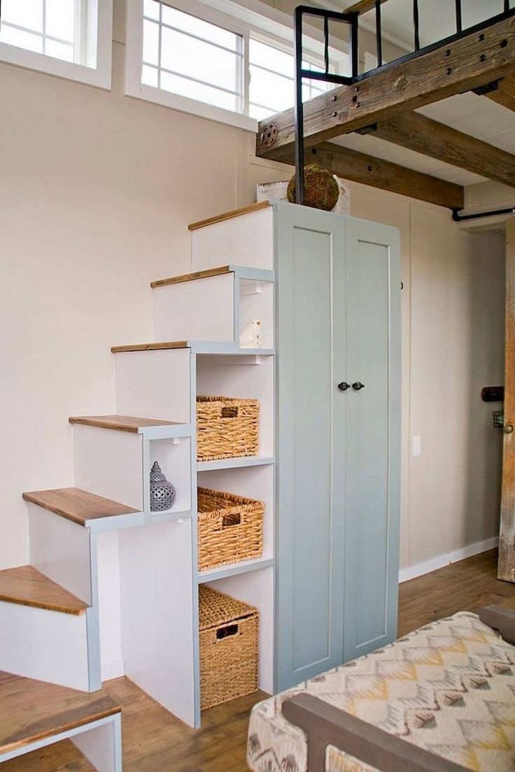 Originally designed stairs at the two-level apartment with built-in cabinet with drawers