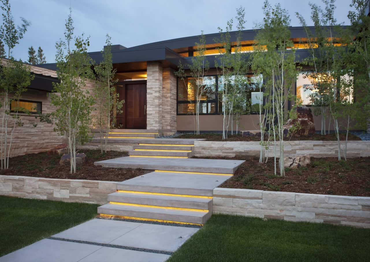 How to Increase the Security in Your Home. Modern high-tech stone-cladded house facade with LED lighting and the same lighting of the yard steps