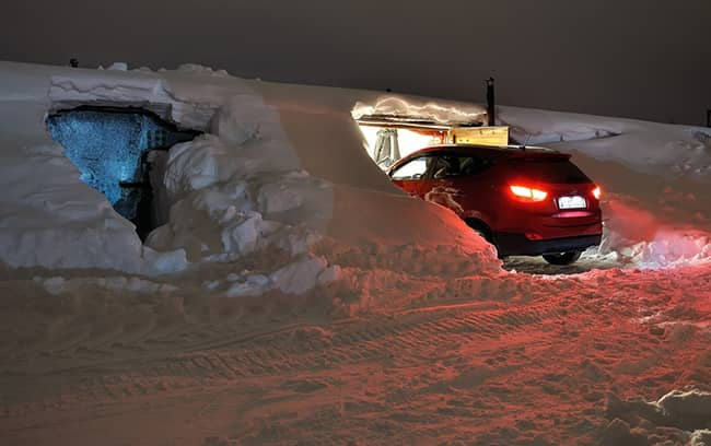 How To Store Your Vehicle in the Winter. garage at the snow pile