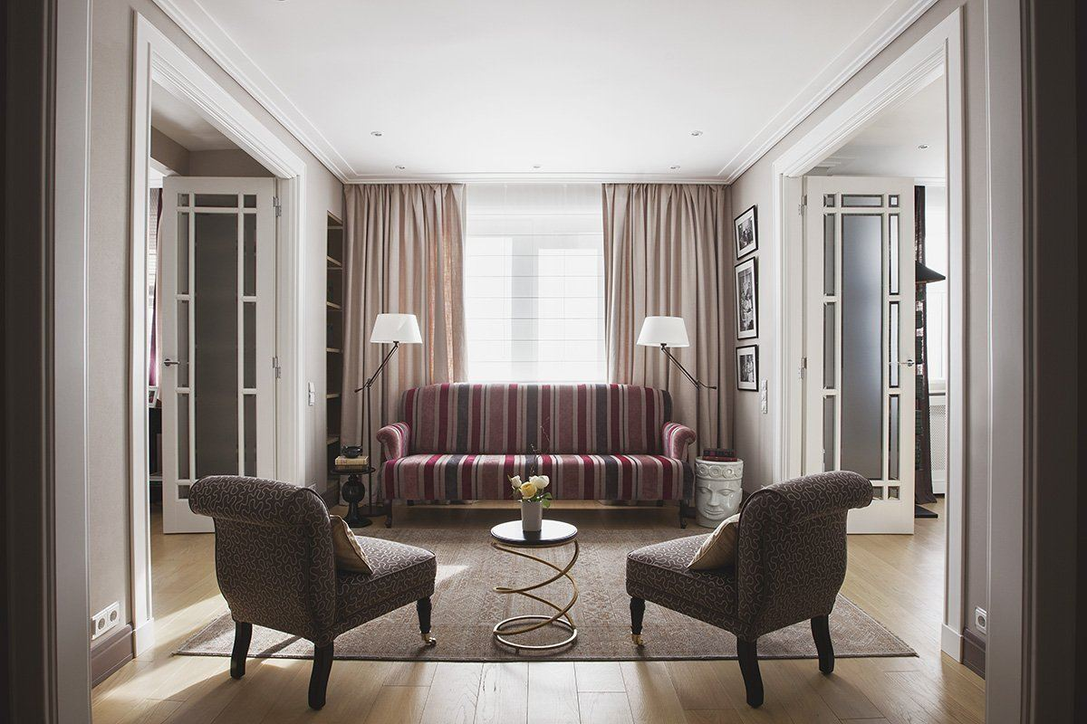 Walk-Through Living Room: Interior Design and Space Zoning. Spacious room with chatting zone made of striped sofa, peculiar table and large armchairs